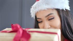 Meisje die van close-up het aantrekkelijke jonge Aziatische Kerstmis Santa Claus-de giftdoos van de hoedenholding met rode boog d