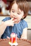 Meisje die van haar verjaardagscake genieten. royalty-vrije stock foto