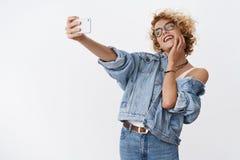 Meisje die van het nemen selfie op nieuwe smartphone genieten, aanbiddend camera en perfect licht voor het goede foto stellen die stock afbeelding