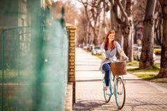 Meisje die van tijd bij het berijden van een fiets tijdens de lentedag genieten in CIT Stock Afbeeldingen