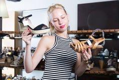 Meisje die van twee paren schoenen in boutique kiezen Stock Fotografie