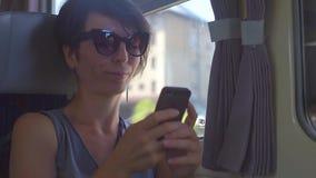 Meisje die in vervoer een mobiele telefoon duwen stock video