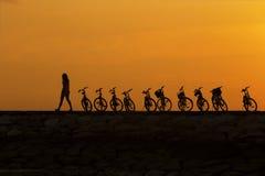 Meisje die voorbij fiets bij pier tijdens zonsopgang lopen stock foto's