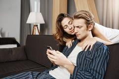 Meisje die vriend proberen te troosten en te toejuichen terwijl hij zitting somber, het scrollen voer in smartphone De echtgenoot royalty-vrije stock foto