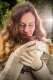 Meisje die in warme kleren op de herfstpark met een kop van heet t genieten van stock fotografie