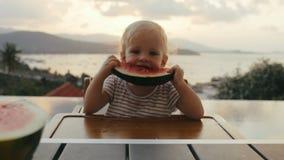 Meisje die watermeloen op openluchtterras op achtergrondavondzonsondergang eten stock footage