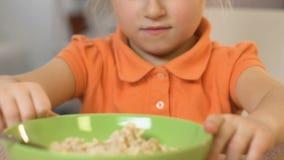 Meisje die weigeren havermeel te eten, die afschuw, gezonde voeding voor jonge geitjes voelen stock video