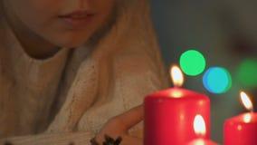 Meisje die wens maken voor Kerstmis en uit kaarsen, geloof in mirakel blazen stock videobeelden