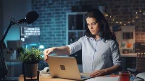 Meisje die werkplaats verlaten bij laptop en lamp uitzetten en nacht die weggaan stock footage