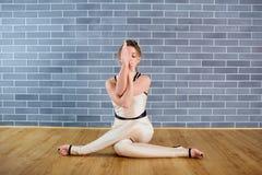 Meisje die in witte kleren de positie van yogagomukhasana inzake flo zitten royalty-vrije stock afbeeldingen