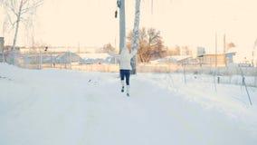 Meisje die witte laag dragen die in sneeuwpark lopen in slowmotion stock videobeelden