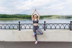 Meisje die yoga doen in openlucht en zich in het bevinden stelt stock foto's