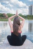 Meisje die yoga op een rots voor het meer op een mooie dag in een park doen Royalty-vrije Stock Afbeelding