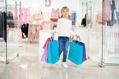 Meisje die zakken houden en camera bekijken terwijl het winkelen stock foto's