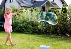 Meisje die zeepbels in huistuin maken royalty-vrije stock fotografie