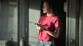 Meisje die zich aan de gang en smartphone bevinden gebruiken stock footage