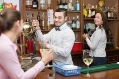 Meisje die zich bij bar met glas wijn bevinden Stock Fotografie