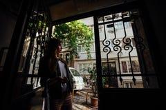 Meisje die zich in de deuropening aan de straat bevinden Krasivayavintazhnayabars op de vensters Mening van de mooie smalle straa stock foto's