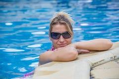 Meisje die zich in een zwembad bevinden stock afbeelding