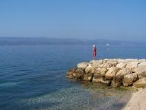 Meisje die zich op de rotsen bevinden die op het overzees letten Stock Foto