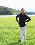 Meisje die zich op weide door meer bevinden Stock Foto
