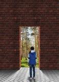 Meisje die zich voor die een muur met een deuropening bevinden door een mooi pijnboombos wordt gevolgd royalty-vrije stock foto