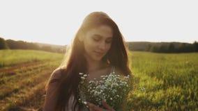 Meisje die zich in weide met boeket van wilde bloemen bij zonsondergang op een de zomeravond bevinden stock footage