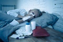 Meisje die ziek in bed liggen die haar neus blazen die ziek met hoge koorts die een koude griep hebben voelen royalty-vrije stock foto