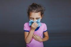 Meisje die zijn neus blazen in zakdoek op grijs stock fotografie