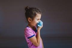 Meisje die zijn neus blazen in zakdoek op grijs royalty-vrije stock fotografie