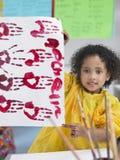 Meisje die Zijn Vinger het Schilderen in Klasse voorstellen Royalty-vrije Stock Foto