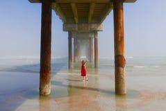 Meisje die zonlicht van kleuren genieten onder een oceaanpijler Royalty-vrije Stock Fotografie