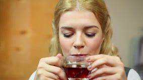 Meisje die zwarte thee van de glaskop drinken Gelukkig wijfje die hete drank proeven stock video
