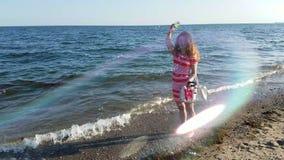 Meisje door de oceaan blazende bellen stock video