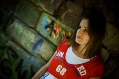 Meisje door muur Stock Foto's