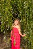 Meisje door wilgentakken die wordt omringd Royalty-vrije Stock Afbeelding