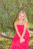 Meisje door wilgentakken die wordt omringd Stock Fotografie