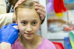 Meisje doordrongen oor in de schoonheidssalon Aanbiddelijk meisje dat oor het doordringen proces met speciaal langs materiaal in  royalty-vrije stock foto