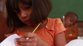 Meisje draaiende pagina's in klaslokaal bij haar bureau stock footage
