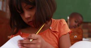 Meisje draaiende pagina's in klaslokaal bij haar bureau stock video