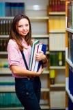 Meisje in een bibliotheek Stock Foto's