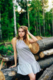 Meisje in een blauwe kleding dichtbij een gevallen boom op een achtergrond van een bos in de zomerweer, een houten speeksel van e Royalty-vrije Stock Afbeeldingen