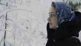 Meisje in een blauwe sjaal in het de winterbos die de rol en de lach repeteren stock video
