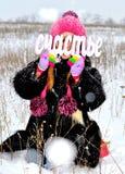 Meisje in een bontjas en hoed in de sneeuw met royalty-vrije stock afbeeldingen