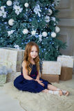 Meisje in een elegante kledingszitting bij de Kerstboom Royalty-vrije Stock Afbeeldingen