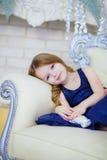 Meisje in een elegante kledingszitting door de open haard Stock Foto's