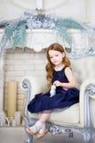 Meisje in een elegante kledingszitting op een stoel Stock Foto's
