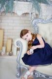 Meisje in een elegante kledingszitting op een stoel en het bekijken de camera Royalty-vrije Stock Afbeeldingen