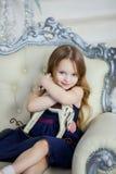 Meisje in een elegante kledingszitting op een stoel en het koesteren van een stuk speelgoed paard Stock Foto