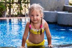Meisje in een geel zwempak in een blauwe pool zoals een meermin jonge geitjesconcept, jonge geitjesmanier stock afbeelding